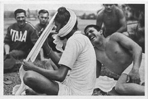 An Indian athlete puts his turban on, entertaining the Italian athletes around him