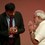India's Prime Minister Narendra Modi gestures to Reserve Bank of India (RBI) Governor Raghuram Rajan at an event on financial inclusion in Mumbai
